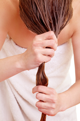 Blonde Frau trocknet ihre langen Haare