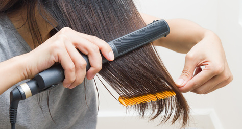 Woman straightening hair with straightener on right hand and comb on left hand.
